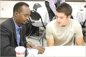 An image with a mentor with  his student reviewing paperwork