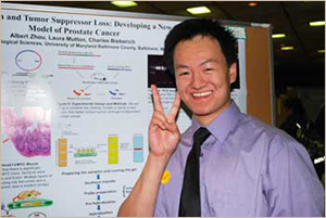 Student standing in front of his presentation board
