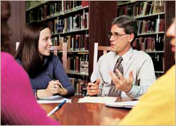 A mentor facilitating a study group in the library